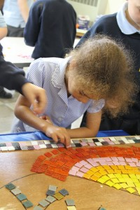 The mosaic follows the design which has been drawn onto the backing board